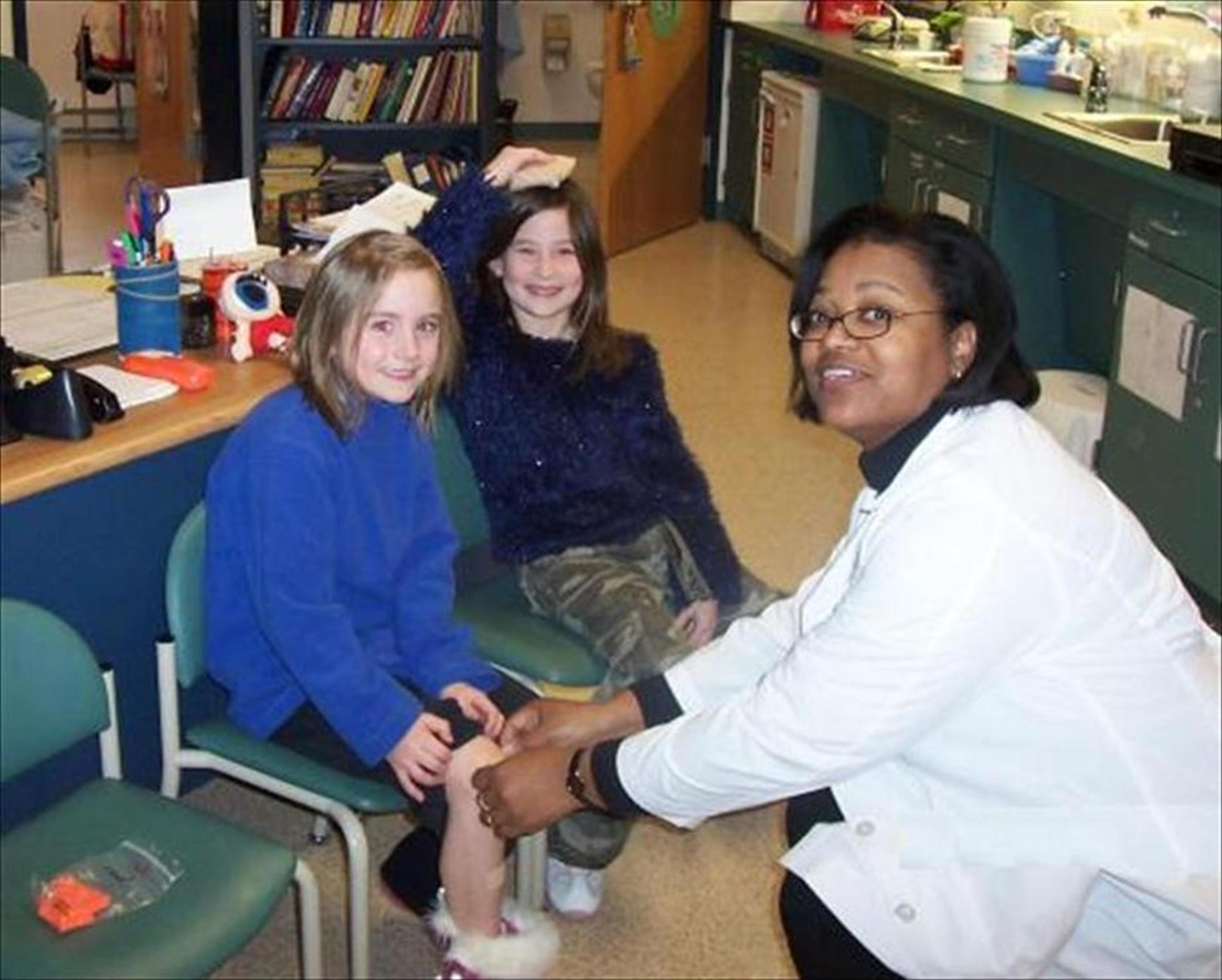 A nurse sits with 2 children and examines 1 of the children's knee.